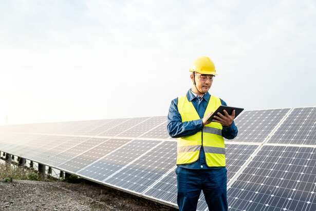 Male engineer holding digital tablet computer in solar photovoltaic power station