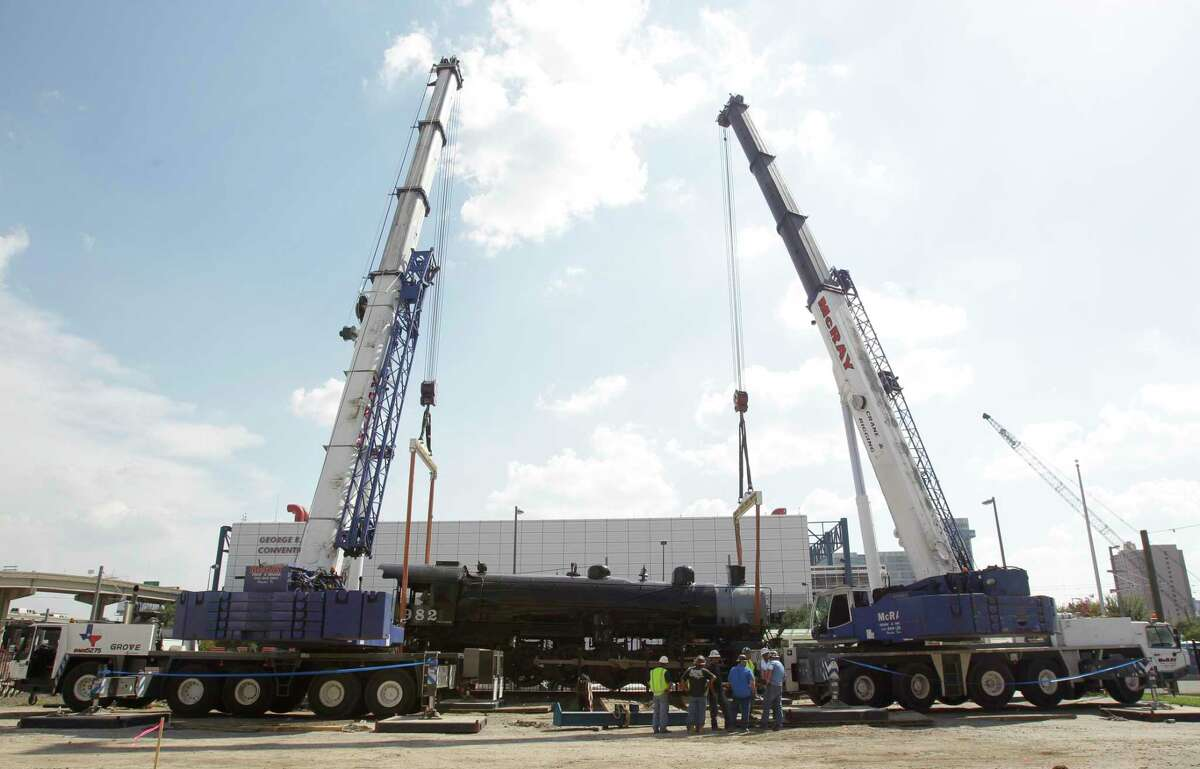 Crews work to move the Southern Pacific 982 steam engine, located downtown between the George R. Brown Convention Center and Minute Maid Park, Wednesday, Aug. 13, 2014, in Houston. The steam engine was hoisted by two 250-ton cranes and placed nearby in a temporary space to allow crews to level the tracks. The engine is scheduled to be moved back onto the tracks on Thursday. ( Melissa Phillip / Houston Chronicle )