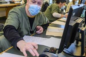 "Health Science students at Hudson Valley Community College recently began volunteering as COVID-19 contact tracers to assist the Rensselaer County Health Department. After completing the Johns Hopkins University's online course, Nursing, Dental Hygiene and Community Health Navigation students are working from a call center on the Troy campus to help curtail the spread of the coronavirus. ""This is a perfect example of how Hudson Valley and its students can serve as a community resource,"" said President Roger Ramsammy. Plus the students are gaining invaluable experience, as well as credit toward the clinical and service learning requirements for their degree. Health Science Dean Patricia Klimkewicz said ""All of the students who participate will learn skills that will serve them in their profession: active listening, ethics, the importance of public health. This is really a unique opportunity: being a health science student during a pandemic and dealing hands-on with a public health crisis."" Pictured in the call center on Feb. 4 is Peter Childs, a nursing student. [HVCC photo: Vincent Giordano]"
