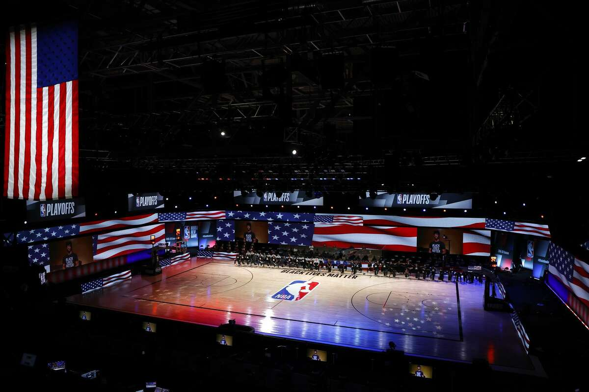LAKE BUENA VISTA, FLORIDA - AUGUST 30: Players take a knee during the national anthem before the start of a game between the Dallas Mavericks and the LA Clippers in Game Six of the Western Conference First Round during the 2020 NBA Playoffs at AdventHealth Arena at ESPN Wide World Of Sports Complex on August 30, 2020 in Lake Buena Vista, Florida. (Photo by Kevin C. Cox/Getty Images)