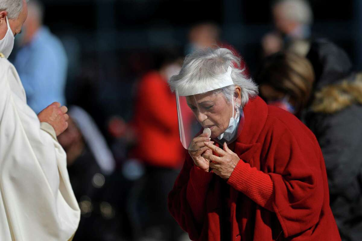 A parishioner, right, takes communion while attending a Christmas Day mass given outdoors in Garden Grove, Calif. Many Catholics and others facing the upcoming Lent are wondering after a year of pandemic sacrifices, what's left to give up?
