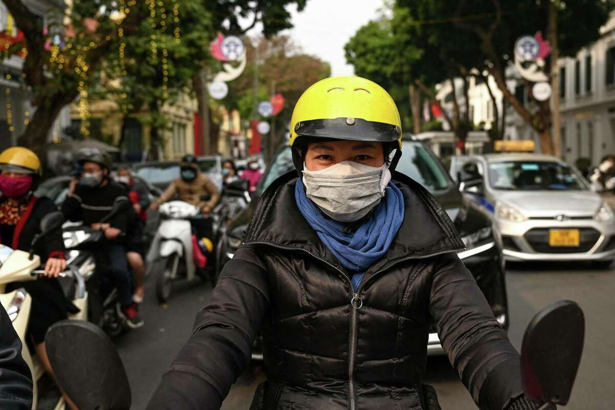 In this file photo taken on January 29, 2021 a woman wearing double protective face masks to prevent the spread of Covid-19 waits at a traffic light in Hanoi, a day after Vietnam recorded its first coronavirus outbreak in almost two months. Wearing two face masks significantly boosts protection against the coronavirus, according to new research by the Centers for Disease Control and Prevention.