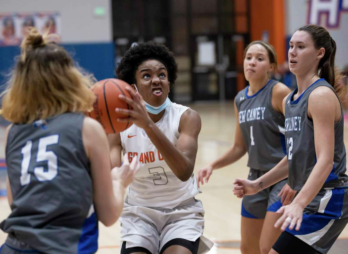 Grand Oaks center Ngozi Agoh (3) shoots the ball while under pressure from New Caney small forward Micha Mize (15) and shooting guard Victoria Edwards (12) during the fourth quarter of a non-district girls basketball game at Grand Oaks High School in Spring.