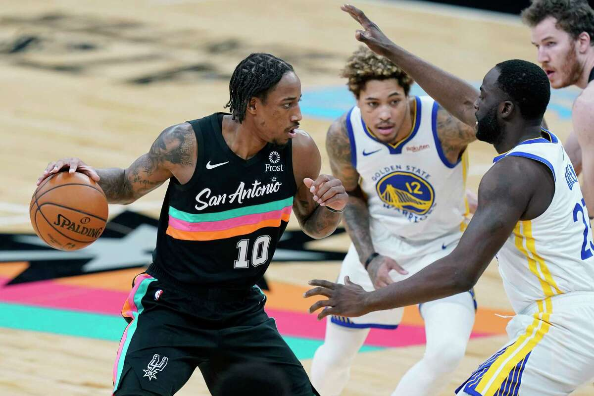 San Antonio Spurs forward DeMar DeRozan (10) is pressured by Golden State Warriors forward Draymond Green (23) during the first half of an NBA basketball game in San Antonio, Tuesday, Feb. 9, 2021. (AP Photo/Eric Gay)
