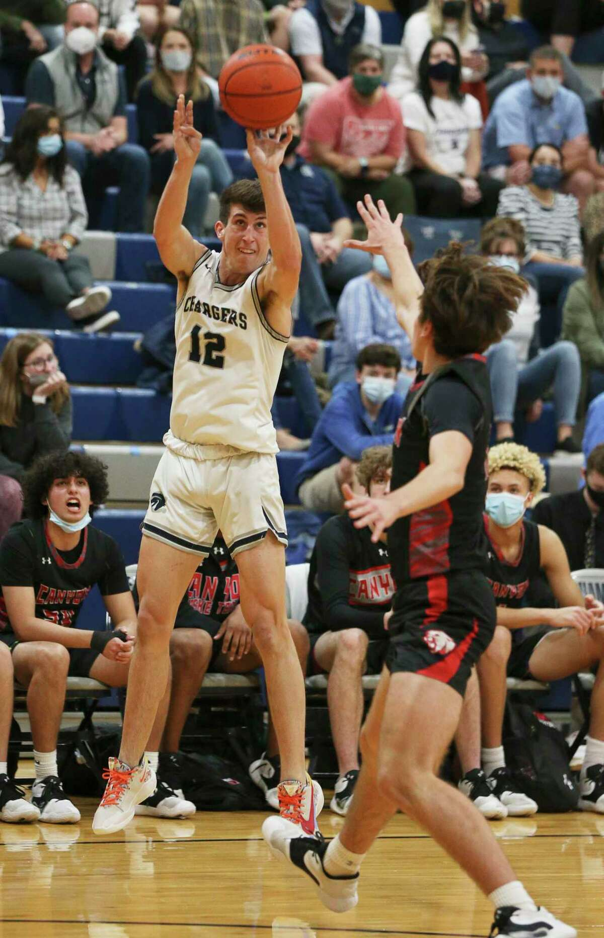 Boerne Champion's Braxton Burdick (12) lines up a three-pointer against New Braunfels Canyon's Mack Bassett (11) in boys basketball in Boerne on Tuesday, Feb. 9, 2021. Boerne Champion defeated NB Canyon, 66-25.