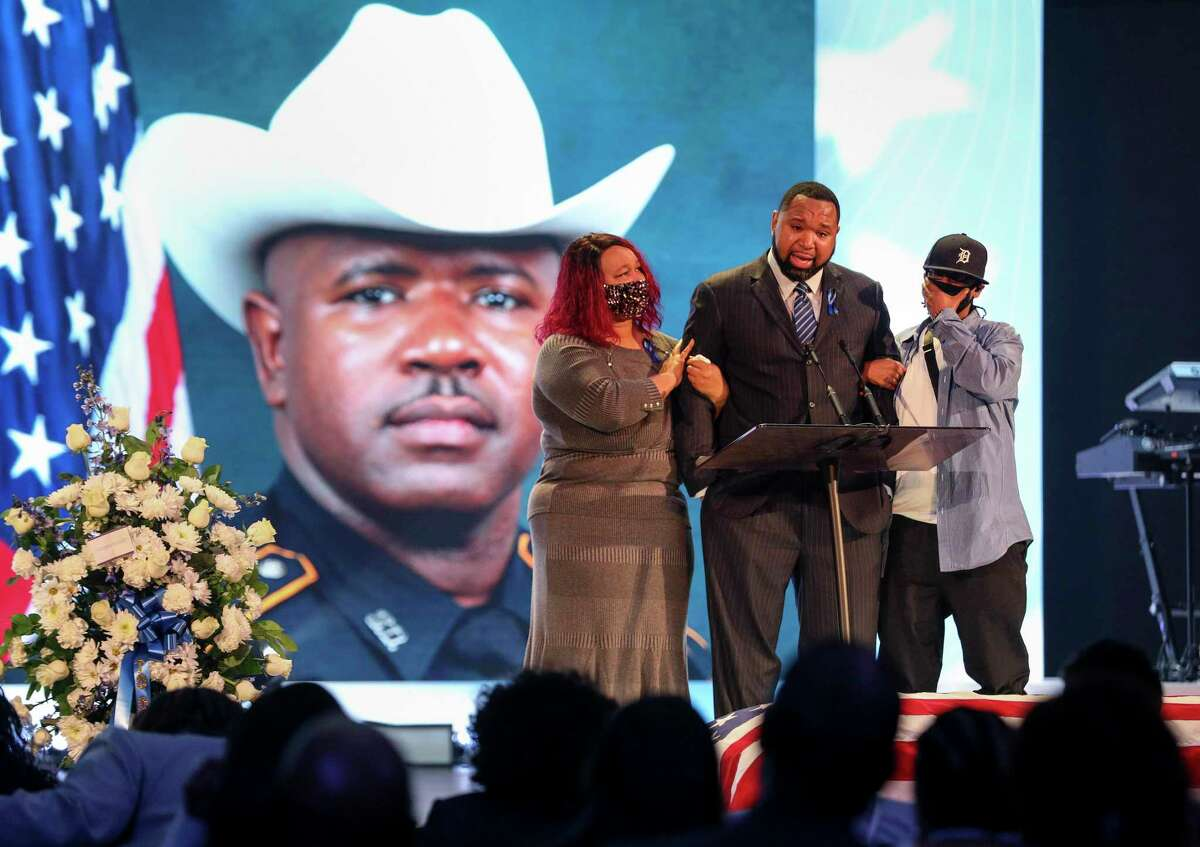 Edwin Watson, flanked by his sisters Musette Watson-Lightner, left, and Trisha Watson, right, becomes emotional while talking about his brother Bruce Watson during his funeral Tuesday, Jan. 12, 2021, at Grace Church in Houston. The Harris County sheriff's sergeant died Jan. 2 after a driver crashed into his motorcycle while he was on his way home from serving as a funeral escort in the Pearland area.