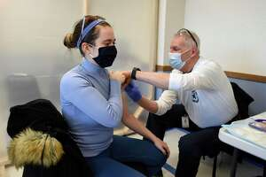 New Haven resident Caroline Beit, an EMT, receives the second dose of her COVID-19 vaccine from Jim Anderson, a member of the GEMS vaccination team, at the Town of Greenwich COVID-19 vaccination clinic at Town Hall in January. Clinics are continuing around town with use of the Moderna and Pfizer vaccines.
