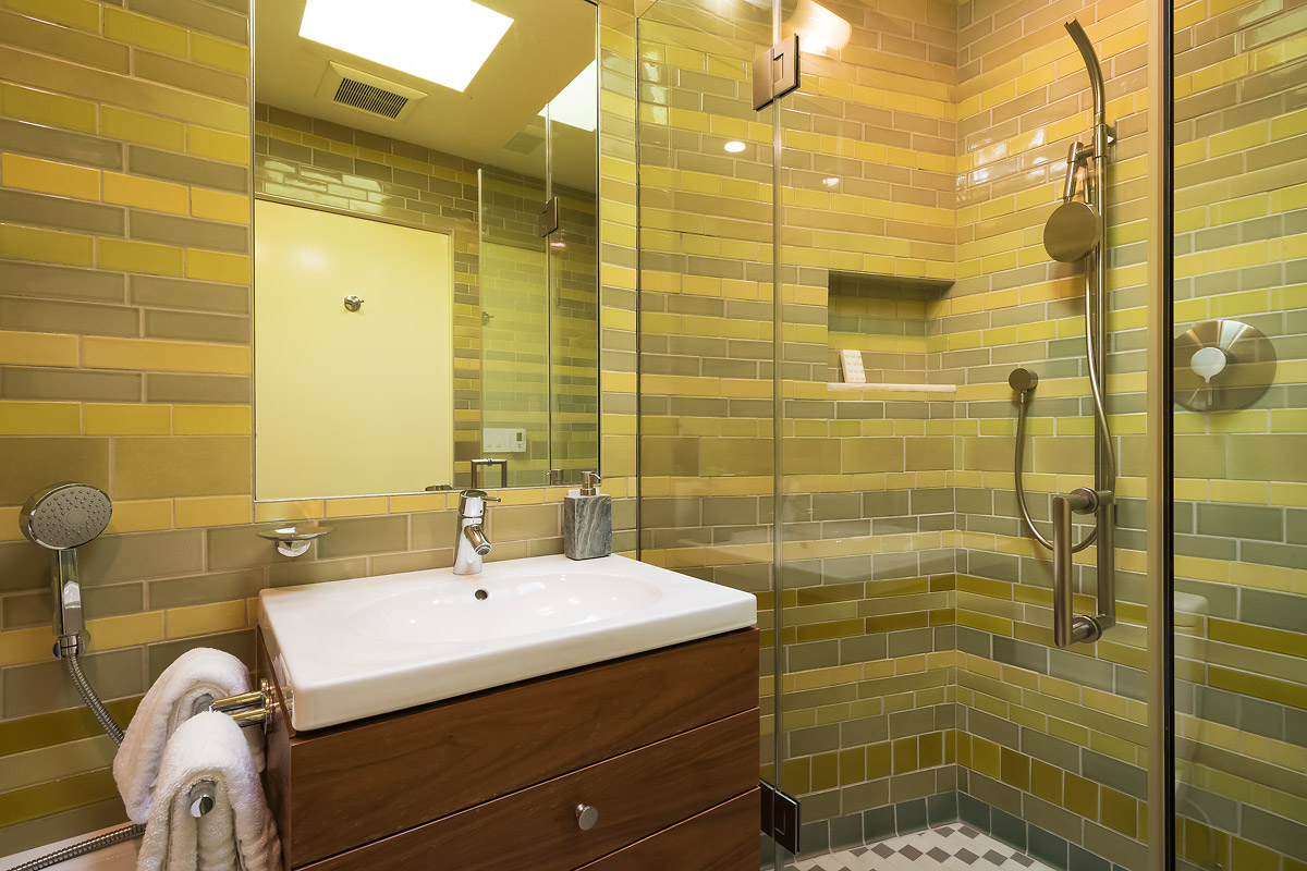 Another bathroom features contrasting tiles and a step-in shower.