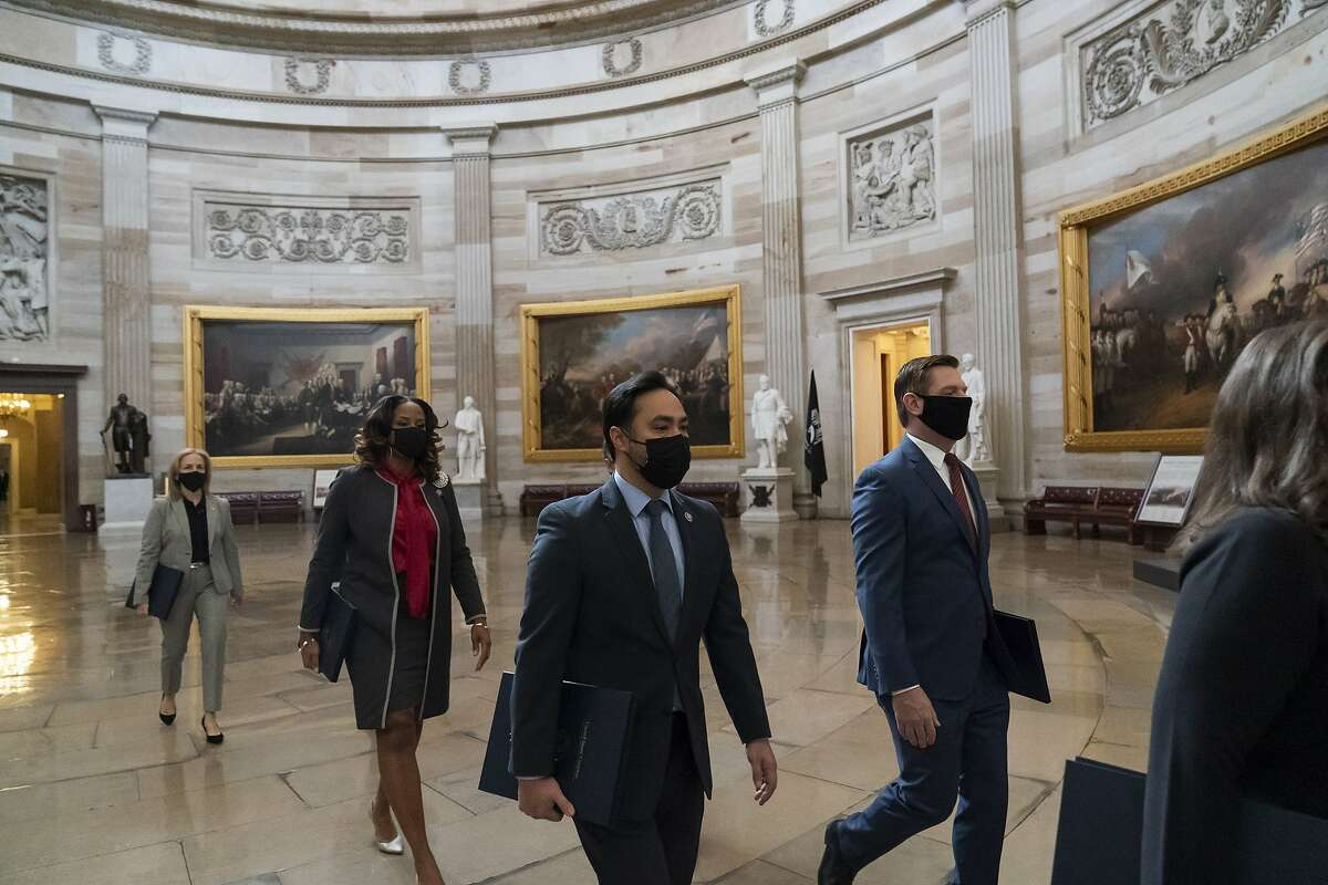 Rep. Eric Swalwell of Dublin (front right), Rep. Joaquin Castro of Texas, Rep. Ted Lieu of Torrance (Los Angeles County), Delegate Stacey Plaskett of the Virgin Islands and Rep. Madeleine Dean of Pennsylvania walk through the Rotunda with the Democrats' other impeachment managers for the trial of former President Donald Trump.