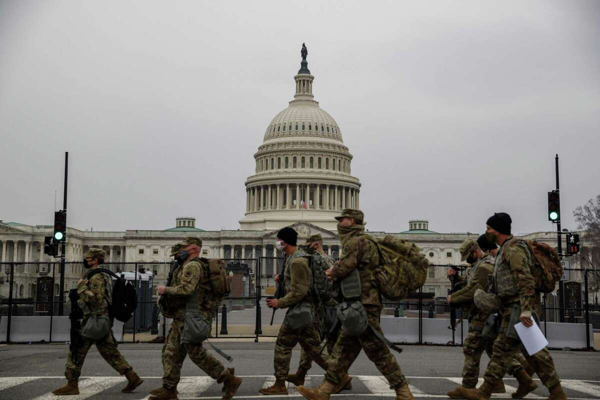 National Guard troops walk past the U.S. Capitol building in Washington, D.C., U.S., on Wednesday, Feb. 10, 2021. House Democrats used searing video footage from last months deadly rampage at the U.S. Capitol to begin Donald Trumps second impeachment trial on a dramatic note, yet the prosecution remains far from winning enough GOP votes to convict the former president. Photographer: Ting Shen/Bloomberg