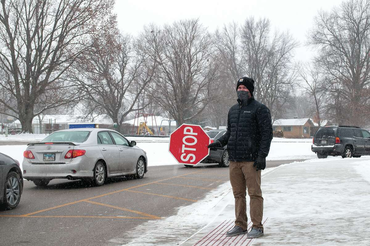 South Jacksonville Elementary teacher Brent Heaton endures snow and cold Wednesday as students are picked up after school. Temperatures are expected to drop into the weekend, with wind chill indices below zero and as low as minus 30 degrees overnight Sunday.
