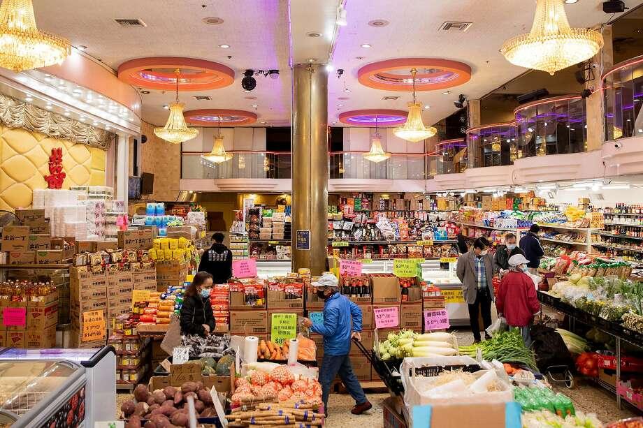 在三藩市华埠的新亚洲大酒楼,购物者在货架选购。该餐馆已改为一家挂着水晶灯的杂货店。Photo: Jessica Christian / The Chronicle
