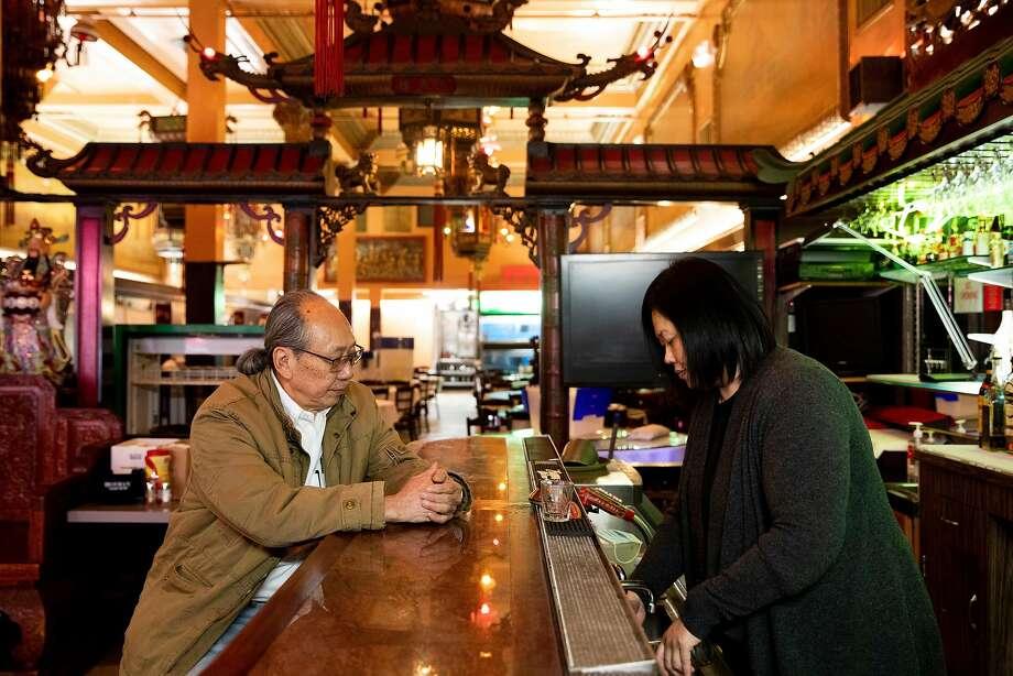 康年海鲜酒家东主李彪坐在酒吧吧台,任职酒家经理的女儿Kathy Lee为他准备饮料。康年是华埠仅存的大型宴会酒家之一,但李彪不知道还能维持营业多久。 Photo: Jessica Christian / The Chronicle