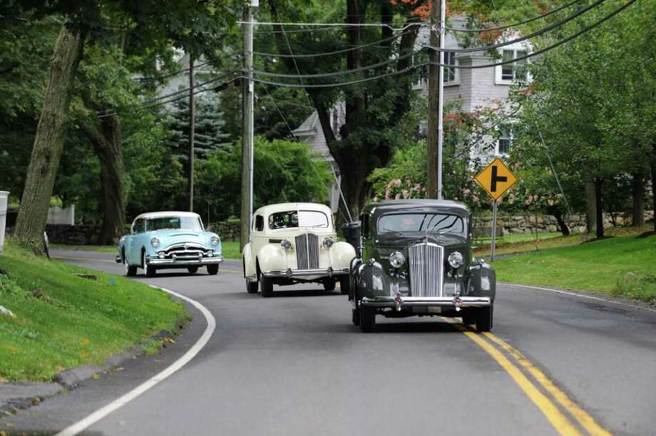 A line of antique cars proceed up the road toward the Fairfield County Hunt Club in Westport during the 2009 Nutmeg Tour for Autism, a fundraising element of the annual car show. Photo: Contributed Photo / Westport News