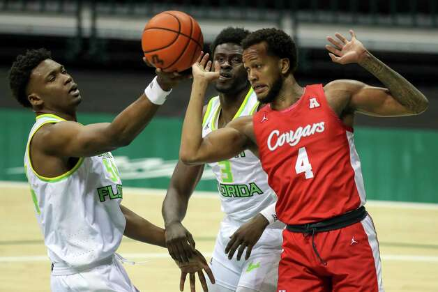 South Florida's Russel Tchewa, left, grabs a rebound in front of Houston's Justin Gorham (4) as South Florida's Prince Oduro (3) looks on during the first half of an NCAA college basketball game Wednesday, Feb. 10, 2021, in Tampa, Fla. (AP Photo/Mike Carlson) Photo: Mike Carlson, Associated Press / Copyright 2021 The Associated Press. All rights reserved