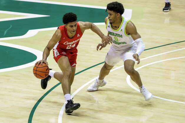 Houston's Quentin Grimes, left, drives past South Florida's David Collins during the first half of an NCAA college basketball game Wednesday, Feb. 10, 2021, in Tampa, Fla. (AP Photo/Mike Carlson) Photo: Mike Carlson, Associated Press / Copyright 2021 The Associated Press. All rights reserved