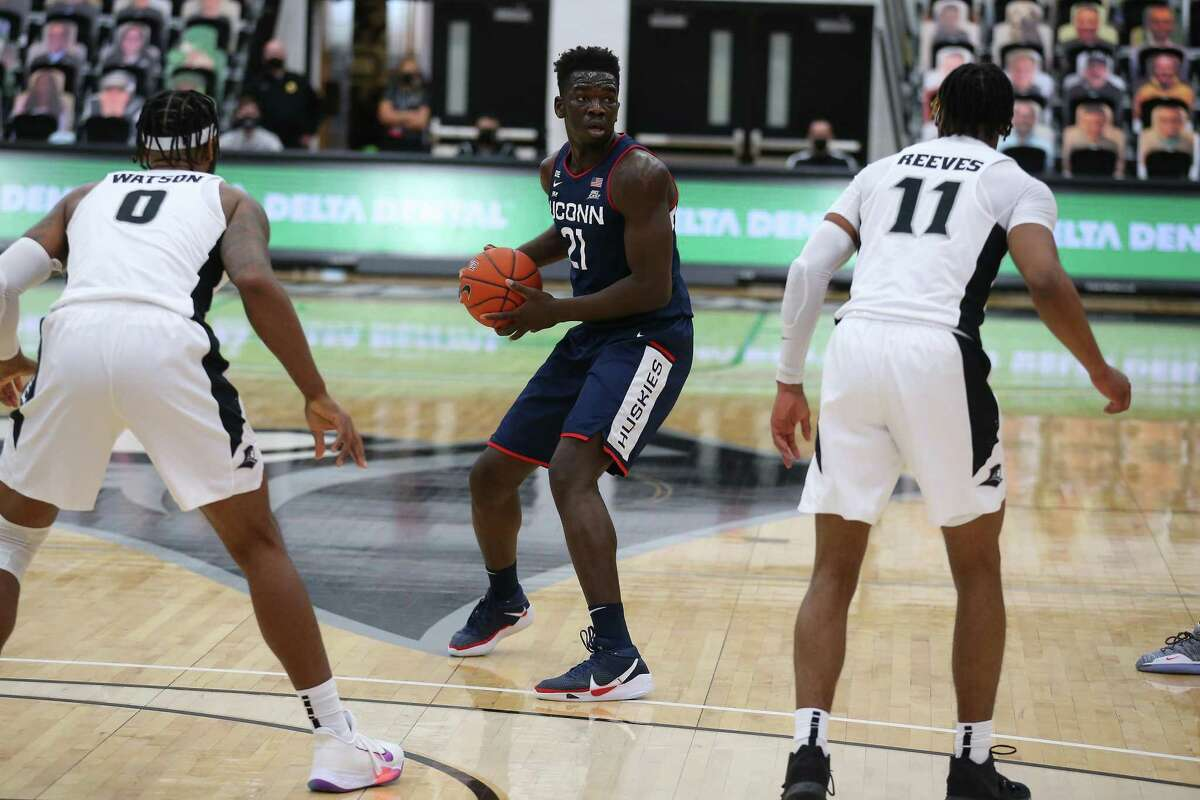 UConn's Adama Sanogo (21) looks to pass while defended by Providence's Nate Watson (0) and A.J. Reeves (11) on Wednesday. UConn at Providence in an NCAA basketball game, Wednesday, Feb. 10, 2021, in Providence, RI. (Photo/Stew Milne)