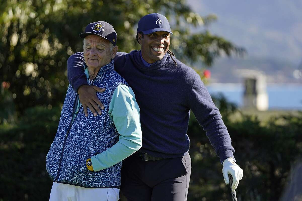 Bill Murray is embraced by Larry Fitzgerald on the first tee during a charity event at Pebble Beach on Wednesday,