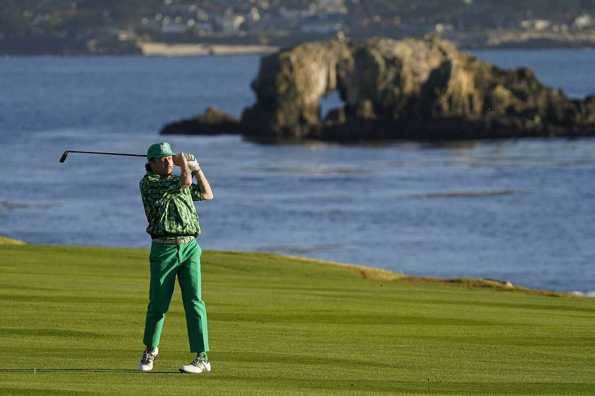 Macklemore watches his shot from the 18th fairway during the charity challenge event of the AT&T Pebble Beach Pro-Am golf tournament Wednesday, Feb. 10, 2021, in Pebble Beach, Calif. (AP Photo/Eric Risberg)