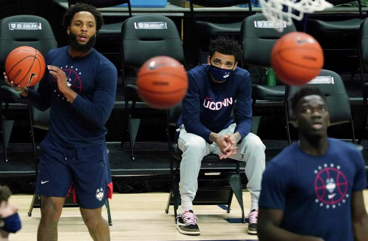 Connecticut guard James Bouknight, middle, looks on from the sideline as his teammates warm up before an NCAA college basketball game against Butler Tuesday, Jan. 26, 2021, in Storrs, Conn. (David Butler II/Pool Photo via AP)