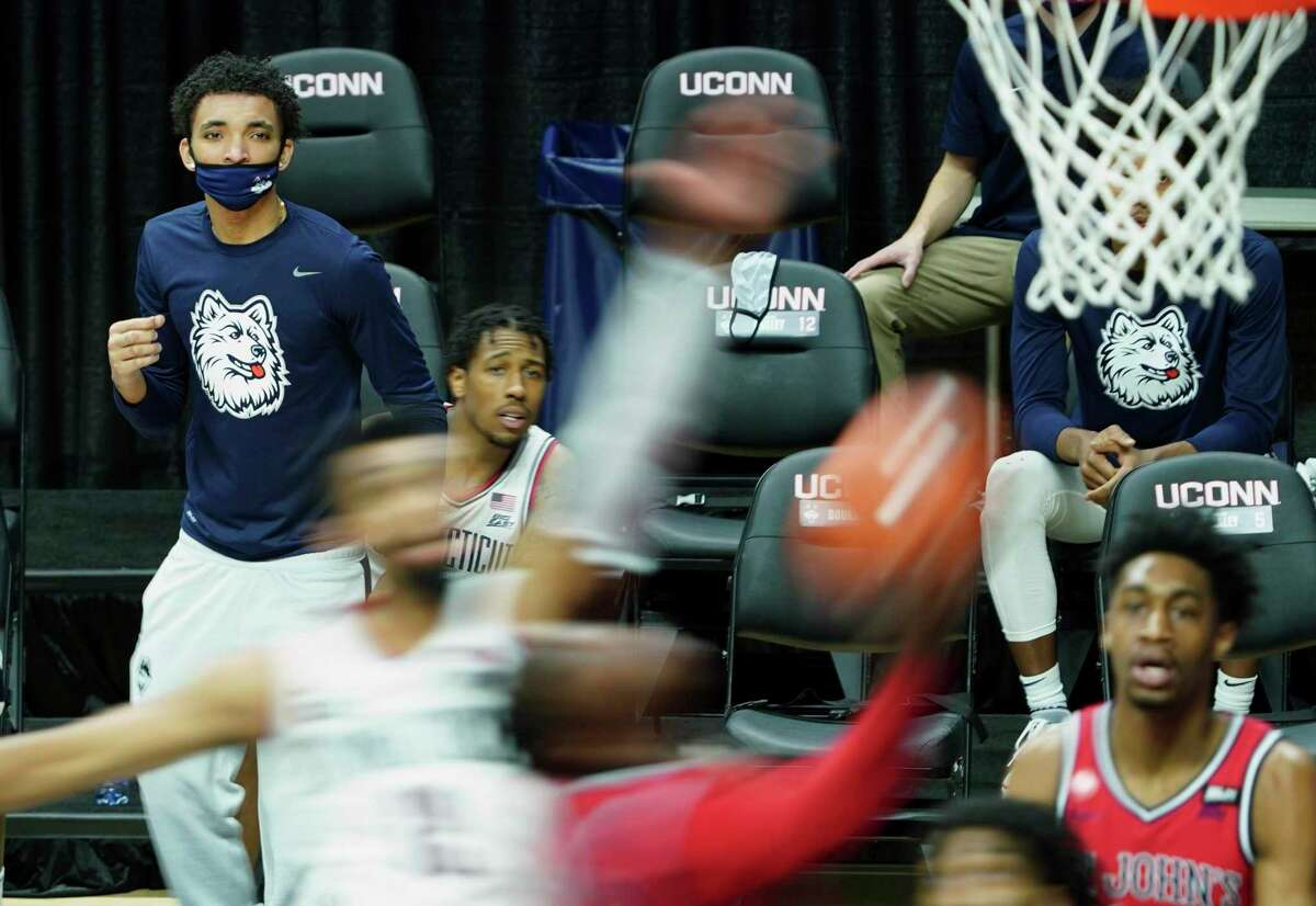 Connecticut guard James Bouknight, left, watches from the sideline as his teammates take on St. John's in the first half of an NCAA college basketball game Monday, Jan. 18, 2021, in Storrs, Conn. (David Butler II/Pool photo via AP)
