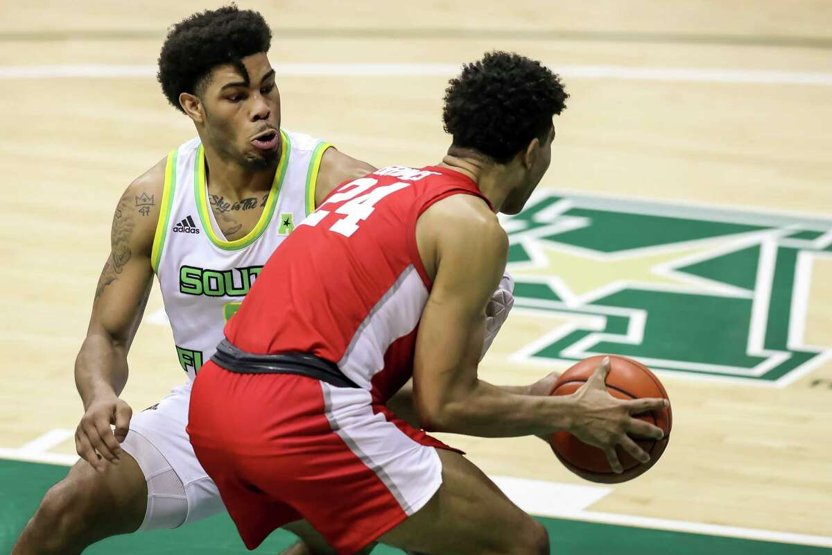 Houston's Quentin Grimes (24) drives against South Florida's David Collins during the second half of an NCAA college basketball game Wednesday, Feb. 10, 2021, in Tampa, Fla. Houston won 82-65. (AP Photo/Mike Carlson)