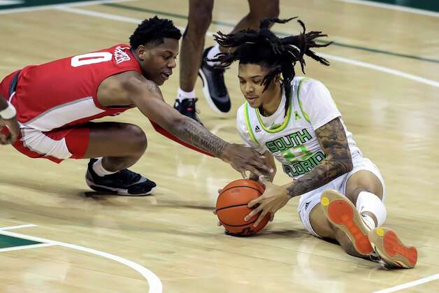 Houston's Marcus Sasser (0) dives for a loose ball with South Florida's Caleb Murphy during the second half of an NCAA college basketball game Wednesday, Feb. 10, 2021, in Tampa, Fla. Houston won 82-65. (AP Photo/Mike Carlson) Photo: Mike Carlson, Associated Press / Copyright 2021 The Associated Press. All rights reserved