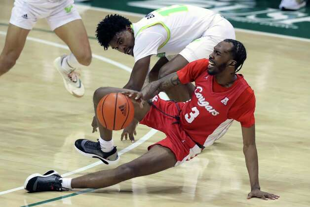 Houston's DeJon Jarreau (3) stumbles past South Florida's Justin Brown during the second half of an NCAA college basketball game Wednesday, Feb. 10, 2021, in Tampa, Fla. Houston won 82-65. (AP Photo/Mike Carlson) Photo: Mike Carlson, Associated Press / Copyright 2021 The Associated Press. All rights reserved