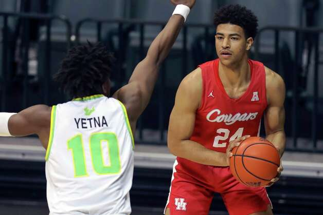 Houston's Quentin Grimes looks to shoot over South Florida's Alexis Yetna during the first half of an NCAA college basketball game Wednesday, Feb. 10, 2021, in Tampa, Fla. Houston won 82-65. (AP Photo/Mike Carlson) Photo: Mike Carlson, Associated Press / Copyright 2021 The Associated Press. All rights reserved