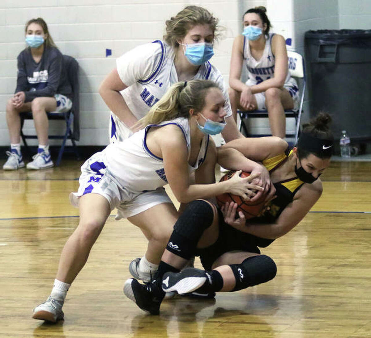 Marquette Catholic's Hayley Porter ties up EA-WR's Mallory Martin (right) for a loose ball in front of the Explorers' Hayley Williams in the first half Wednesday night at Marquette Family Arena in Alton.