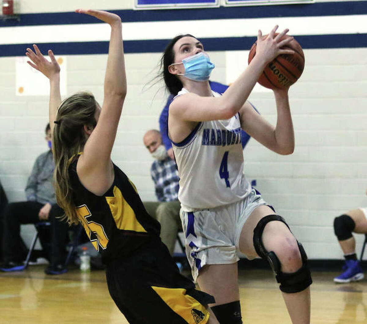 Marquette Catholic's Abby Williams (4) goes in for two of her game-high 19 points while EA-WR's Hannah Allen defends in the third quarter Wednesday night in Alton.