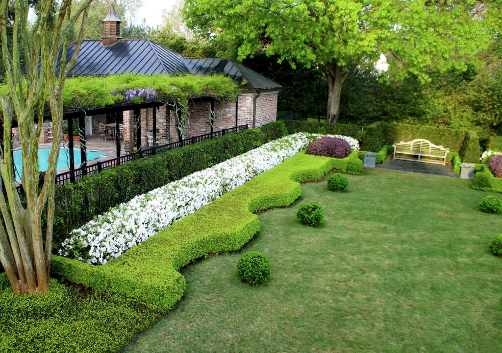 These topiaries and curiously shaped hedges by Lanson B. Jones & Co, Inc produce a memorable garden santucary. The look of this area will stick with your guests, as every angle provides a fun visual element. Trees planted in tall hedges divide the swimming pool area from the backyard garden.