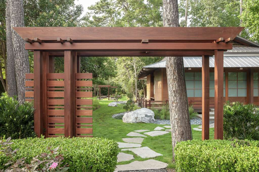 Zen meets hectic Houston at this Exterior Worlds Landscaping & Designbackyard. The Japanese garden and dojo will make Houstonians feel like they're worlds away, just steps from their home. In addition to an Asian-inspired pergola and stone-accented walkway, hedges and tall trees enhance the tranquil space.