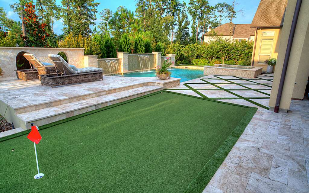 Can't decide between a playground or a scenic pool-adjacent patio? Ask for both from Absolutely Outdoors or mimic their design by installing AstroTurf for a putting green next to outlined pavestone. It's an inviting patio that will entertain golfers and pamper the spa-lovers among us.