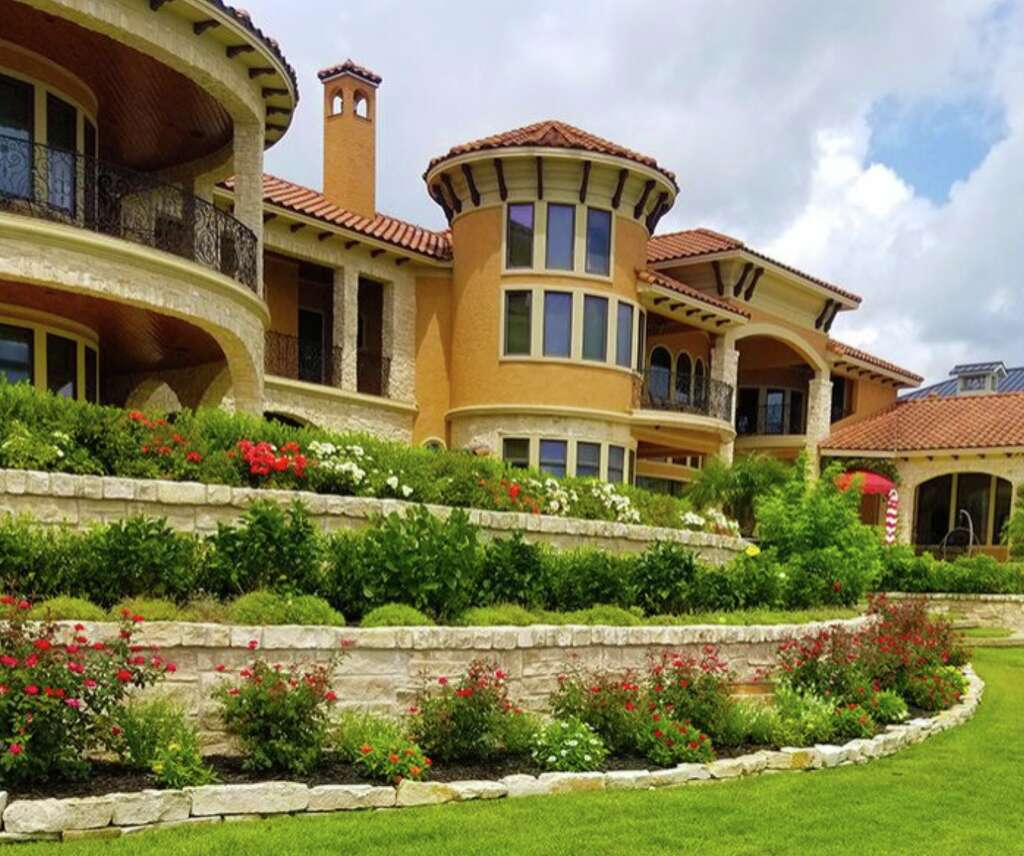 Archer Services knows that tiered, stadium seating-style flowerbeds make for a jaw-dropping yard. The multi-level landscape adds a sense of grandeur appropriate for a house of this magnitude. Alternating greens and blossoms amplify the borders in this patio's design while adorning the estate's facade.