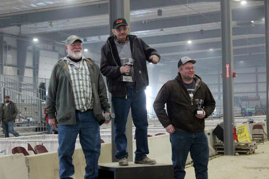 """Mecosta tractor puller Josh Eichenberg stands in the third spot on the podium with the trophy he received for driving his """"G6"""" tractor to a third place finish in the 5,250 pound Heritage Pro Stock Class Finals at the 2021 Midwest Winter Nationals held February 4-6 in the Michiana Events Center (MEC) near Shipshewana, Indiana. Eichenberg's tractor bested 17 other tractors entered in his division. In the Finals on Friday, Eichenberg earned his third place finish beating five other entrants by pulling further on the 300 foot dirt track constructed inside the event center's arena. Additional details and results on other classes at the Midwest Winter Nationals can be found at Whatssmokin.net. (Photo courtesy of George Hubka/MG News Service)"""