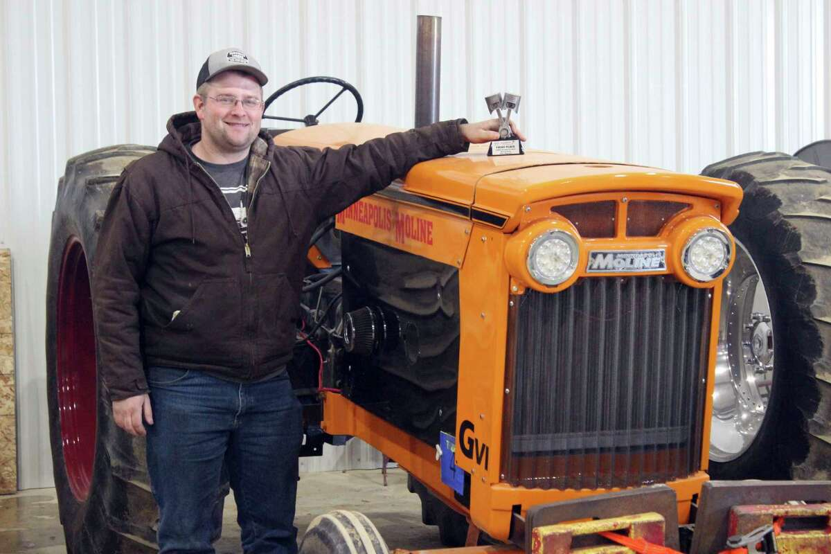"""Josh Eichenberg, of Mecosta, stands beside his Minneapolis Moline with the trophy he earned for driving his """"G6"""" tractor to a third place finish in the 5,250 pound Heritage Pro Stock Class Finals at the 2021 Midwest Winter Nationals held February 4-6. During the three day event, presented by Whatssmokin Promotions held at the Michiana Events Center near Shipshewana, Indiana Eichenberg's tractor bested 17 other tractors entered in his division during the prelims on Thursday. In the Finals on Friday,Eichenbergearned his third place finish beating five other entrants by pulling further on the 300 foot dirt track constructed inside the event center's arena. Additional details and results on other classes at the Midwest Winter Nationals can be found at Whatssmokin.net (Photo courtesy of George Hubka/MG News Service)"""