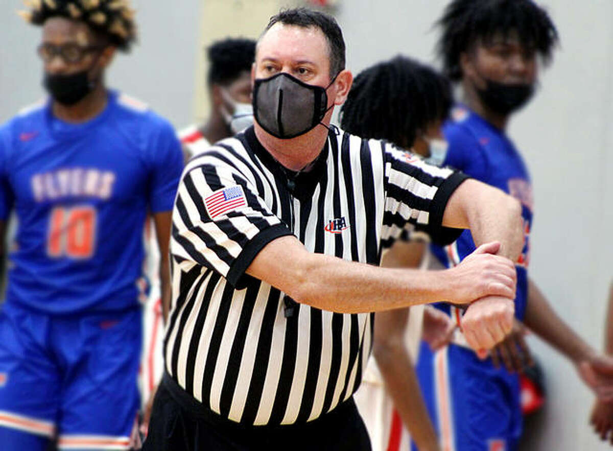 Referee Rod Taylor indicates a holding call during Tuesday night's Southwestern's Conference game at Alton High School between the Redbirds and East St. Louis. Some 37 referees in the Southwestern Athletic Officials Association have opted out of refereeing basketball games this season because of the COVID-19 pandemic.