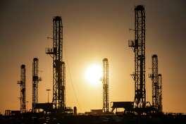 The morning sun rises behind oil rigs sitting in storage Saturday, Feb. 6, 2021 at a yard outside of Odessa, Texas. (Eli Hartman/Odessa American via AP)