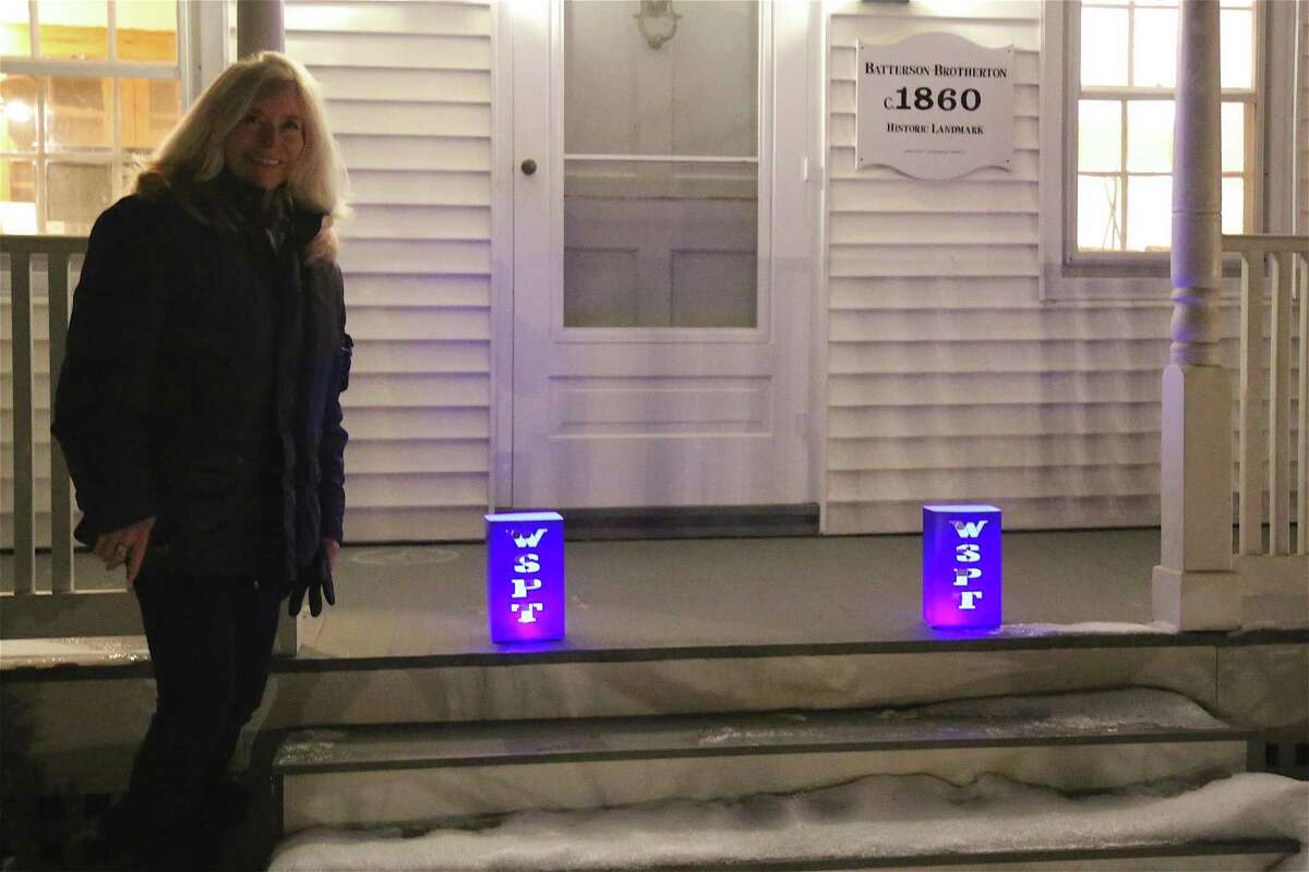 Real estate agent Julie Broder stands outside one of her house listings on Roseville Road where she put up some luminaries as part of the
