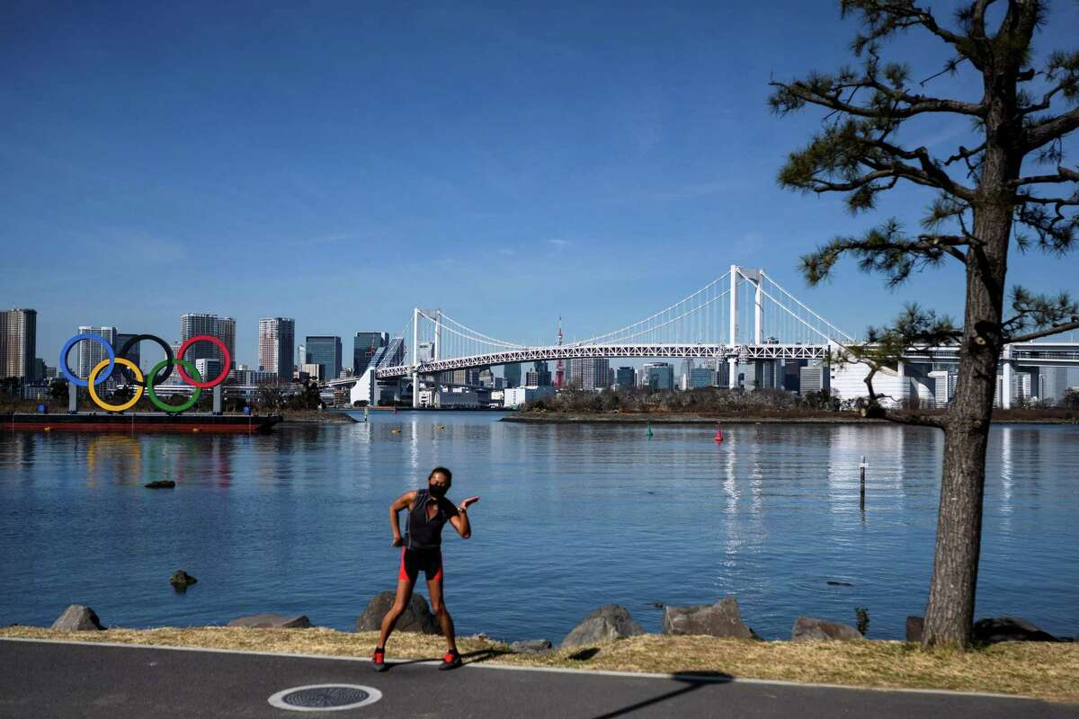 A man dances and records videos near the Olympic rings at the Odaiba waterfront in Tokyo on Feb. 10, 2021. NBC Sports will broadcast live the summer Olympics' opening ceremony on July 23, 2021.