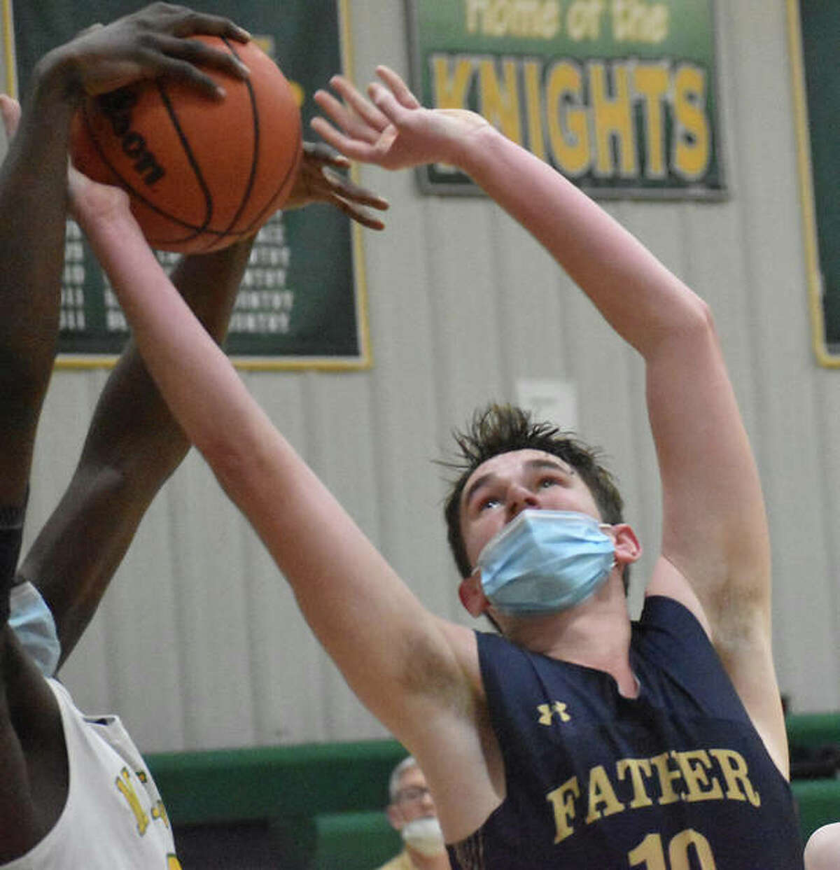 Father McGivney's Justin Wenos battles for a rebound in the first half of Monday's game against Metro-East Lutheran in Edwardsville.