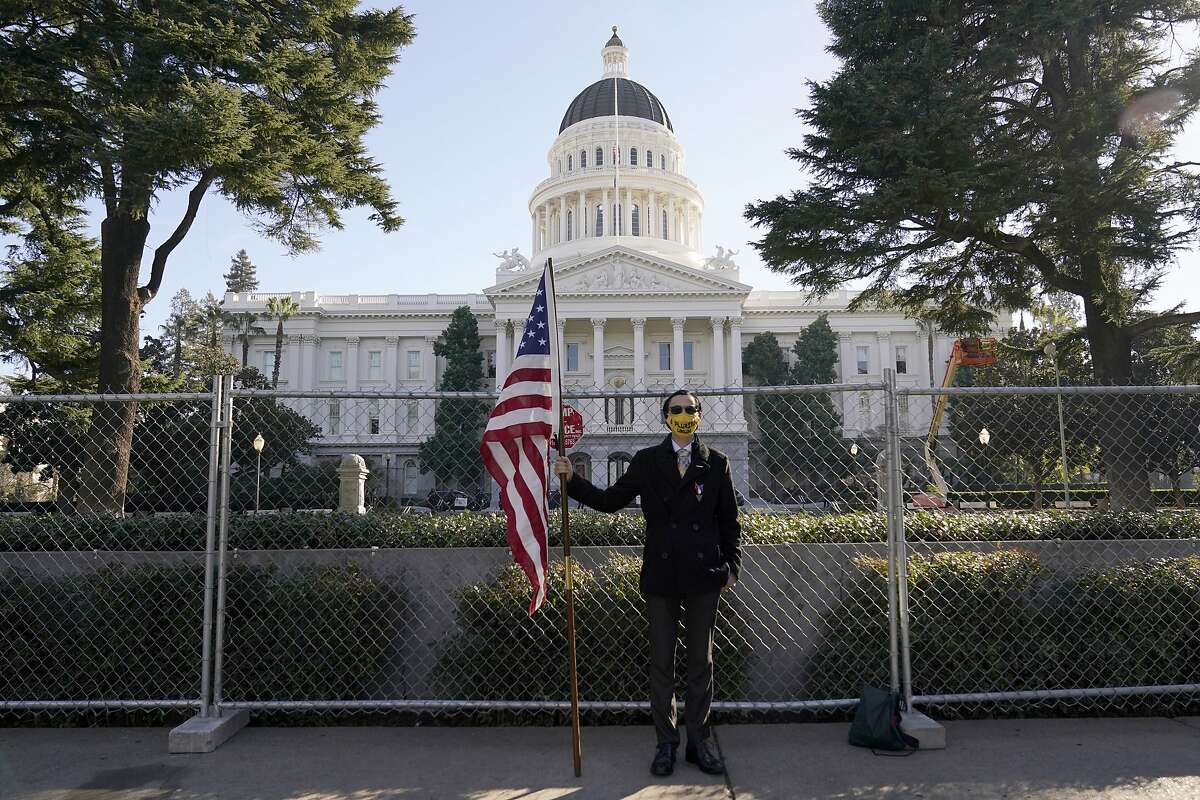 Christian Alvarado holds an American flag as he stands in front of a temporary six-foot high chain link fence surrounding the state Capitol in Sacramento on Jan. 16, 2021.