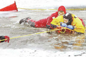 Alton Batallion Fire Chief Matthew Fischer, in yellow, is pulled to safety from the ice cold waters of the pond at the Olin T. Spencer Golf Course where Alton firefighters have been practicing ice training. Firefighters took advantage of the frigid weather to do the training not possible in recent years due to mild winters. Fischer, who doubled as both instructor and mock victim, was pulled out of the water on a specialized sled used for ice rescues by firefighters wearing protective wetsuits.