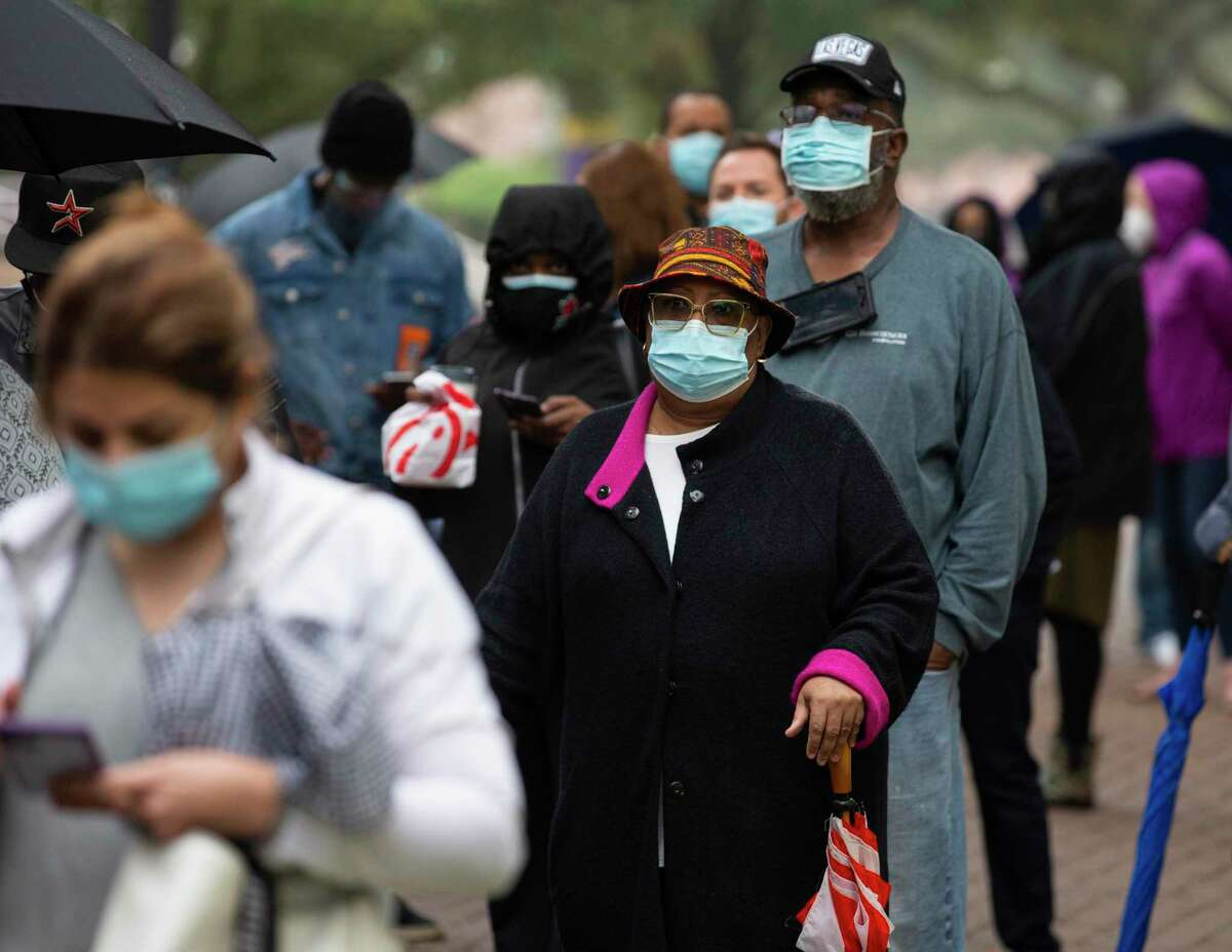 People wait in a long line in hope to get free Pfizer COVID-19 vaccines at Texas Southern University Wednesday, Feb. 10, 2021, in Houston. Texas Southern University and Baylor-St. Luke's Medical Center will officially launch a COVID-19 vaccination site next week at the Third Ward-based college.