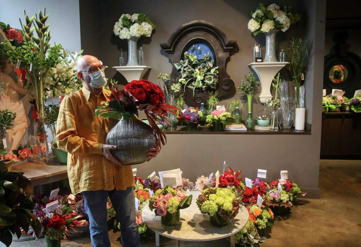 David Brown shows off a large vase with red roses Thursday, Feb. 11, 2021, at David Brown Flowers in Houston. Brown said his flower shop has been open for 45 years, in different locations.