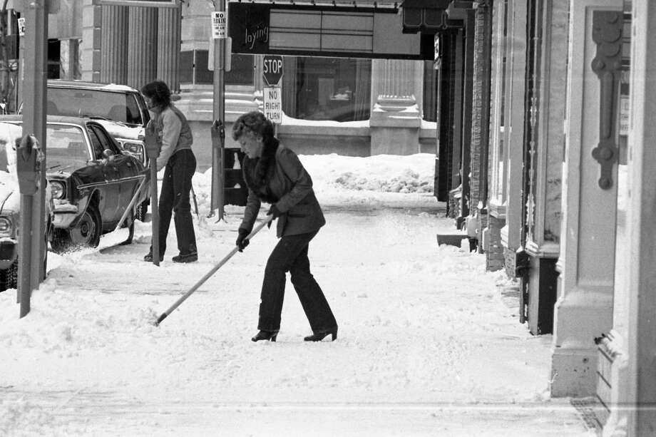 Shown hereare two peopleshoveling snow on River Street near the corner of Poplar Street in early February 1981. (Manistee County Historical Museum photo)