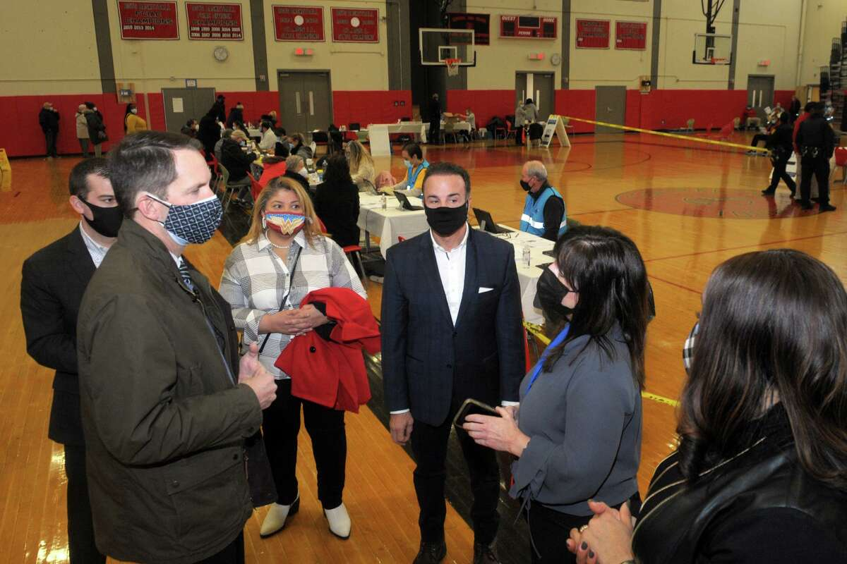 Acting Deputy Health Director Tammy Papa, second from right, speaks with US Rep. Jim Himes, City Council President Aidee Nieves and Mayor Joe Ganim during a visit to the weekly vaccination clinic held in the gymnasium of Central High School in Bridgeport, Conn. Feb. 10, 2021.