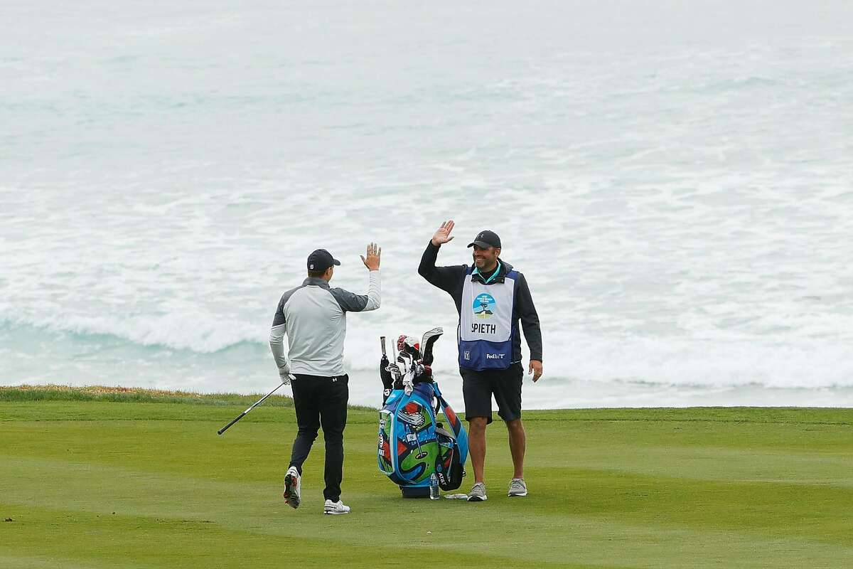 Jordan Spieth and caddie Michael Greller celebrate his eagle on the 10th hole during Thursday's first round of the AT&T Pebble Beach Pro-Am.