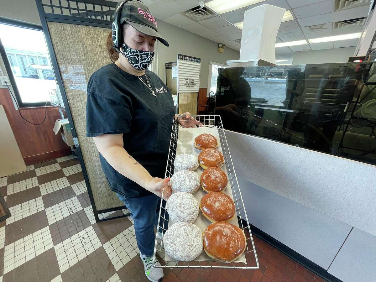 Samantha Henderson displays two different types of paczki -- loaded with 500 delicious calories each -- Bernie's Place will feature on Fat Tuesday. Paczki flavors at Bernie's Place will consist of raspberry, custard, lemon, apple cinnamon and many others. Some will be frosted, and others will don a light powder sugar topping. Grab your favorite Tuesday, Feb. 16, and enjoy. (Pioneer photo/Bradley Massman)